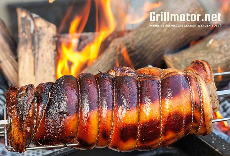 Grillmotor Landmann beim grillen eines Schweinebratens über dem offenen Feuer